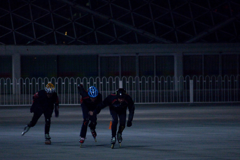 Three competitive skaters practicing at night around cones on the Olymipic Park pedestrian walking mall.