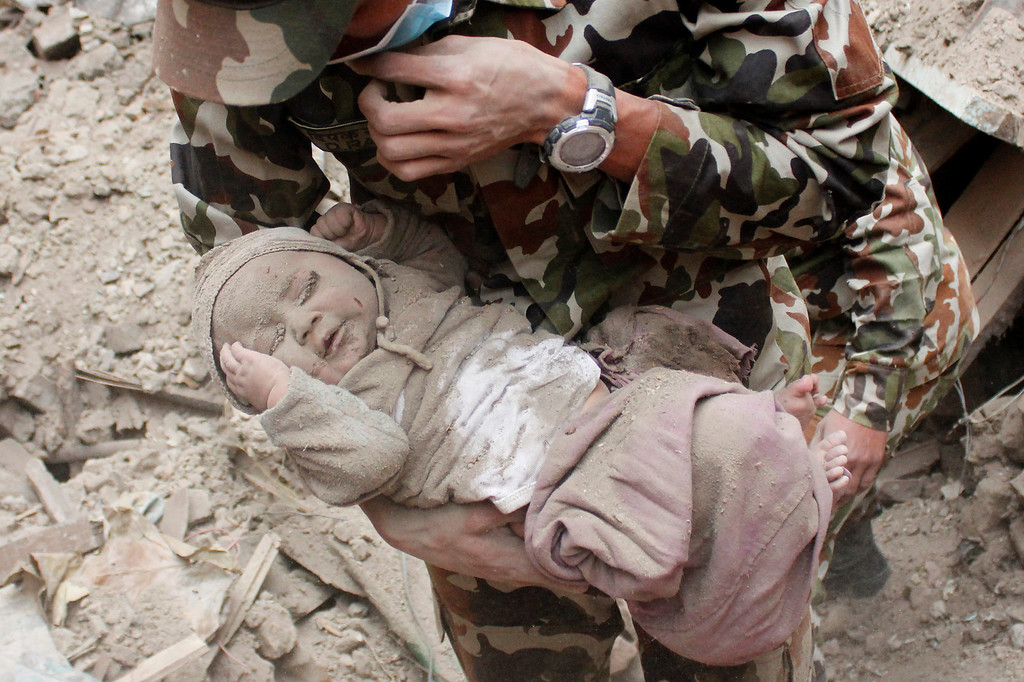 ". In this Sunday, April 26, 2015, photo taken by Amul Thapa and provided by KathmanduToday.com, four-month-old baby boy Sonit Awal is held up by Nepalese Army soldiers after being rescued from the rubble of his house in Bhaktapur, Nepal, after Saturday\'s 7.8-magnitude earthquake shook the densely populated Kathmandu valley.  Thapa says that when he saw the baby alive after 20 hours of rescue efforts�ì� all my sorrow went. Everyone was clapping. It gave me energy and made me smile in spite of lots of pain hidden inside me."" (Amul Thapa/KathmanduToday.com via AP)"