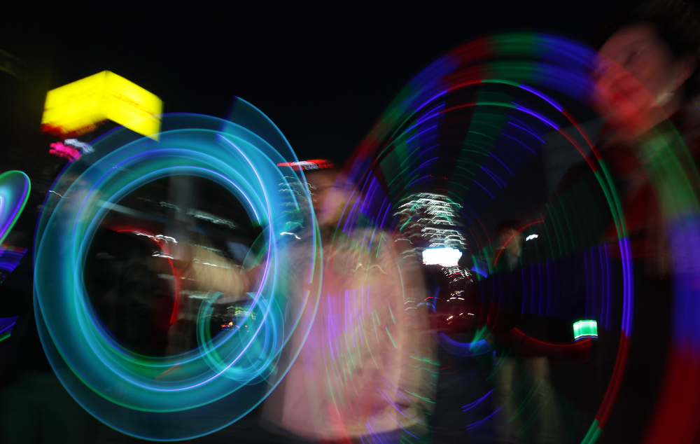 Description of . South Koreans spin illuminated cans during 'Cyber Jwibulnoli' at Everland on February 21, 2013 in Seoul, South Korea. Jwibulnoli is originally played on the first full moon of the lunar year, that is February 25 this year.  (Photo by Chung Sung-Jun/Getty Images)