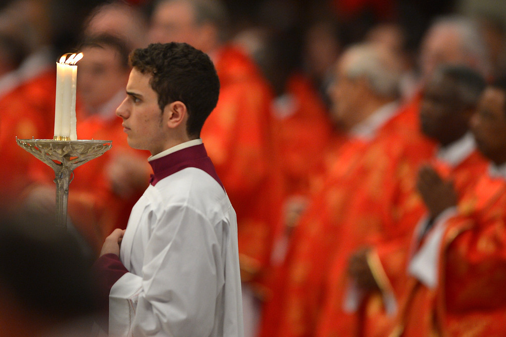 . An assistant holds a candle during a mass at the St Peter\'s basilica before the conclave on March 12, 2013 at the Vatican.  AFP PHOTO / GABRIEL BOUYS/AFP/Getty Images