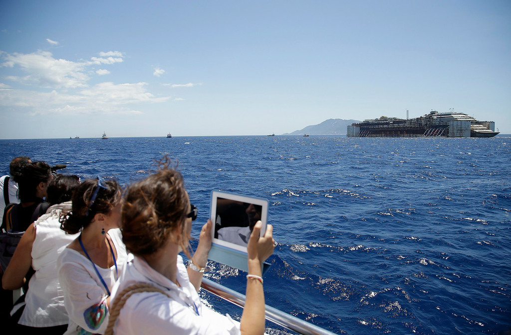 . Reporters take picture of the wreck of the Costa Concordia cruise ship being towed by two tugboats away from the Tuscan island of Isola del Giglio, Italy, Wednesday, July 23, 2014. The Costa Concordia cruise liner has begun its final voyage away from the tiny Italian island where it capsized on Jan. 13, 2012, killing 32 people. (AP Photo/Gregorio Borgia)