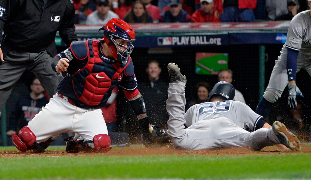 . Cleveland Indians catcher Roberto Perez is late on the tag as New York Yankees\' Todd Frazier scores during the ninth inning of Game 5 of a baseball American League Division Series, Wednesday, Oct. 11, 2017, in Cleveland. (AP Photo/Phil Long)