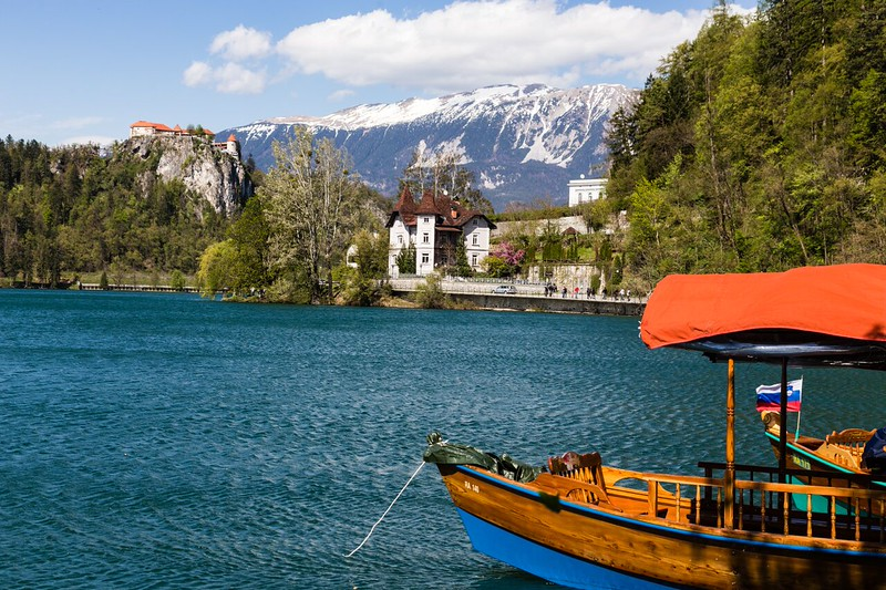 Traditional boat on a lake with castle view and mountains
