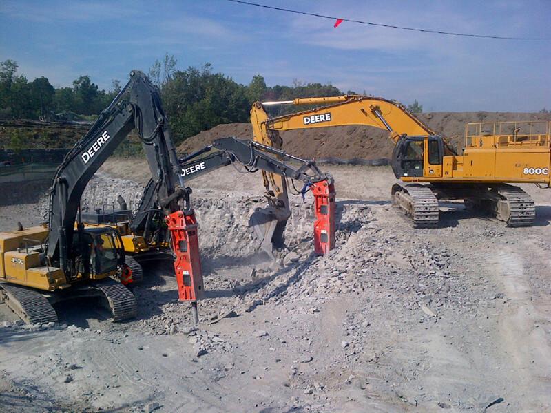 NPK GH18 hydraulic hammer on Deere excavator breaking rock in quarry 1.jpg