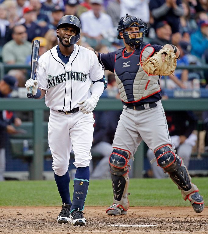 . Seattle Mariners\' Guillermo Heredia, left, turns away from the plate after striking out looking with the bases loaded as Cleveland Indians catcher Yan Gomes returns the ball to the mound to end the sixth inning of a baseball game Saturday, Sept. 23, 2017, in Seattle. (AP Photo/Elaine Thompson)