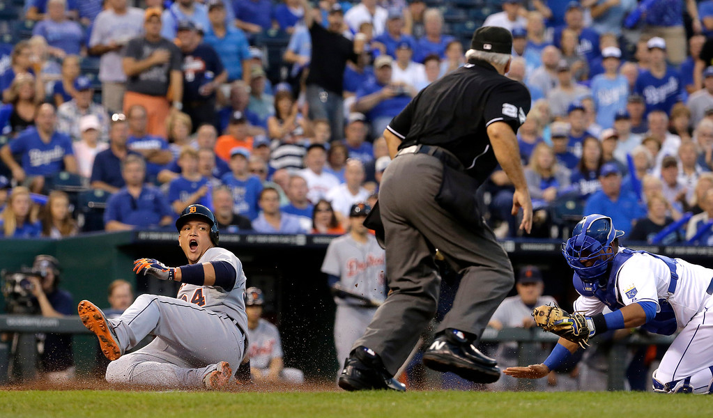 . Detroit Tigers\' Miguel Cabrera slides home past Kansas City Royals catcher Salvador Perez to score on a single by Victor Martinez during the first inning of a baseball game Friday, Sept. 19, 2014, in Kansas City, Mo. (AP Photo/Charlie Riedel)