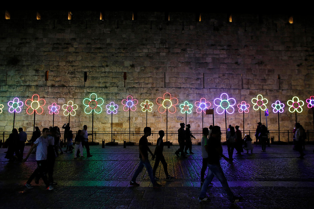 """. People walk past illuminated flowers displayed outside Jerusalem\'s Old City during the \""""Jerusalem Light 2013\"""" Festival June 5, 2013. The festival opened on Wednesday night and will run for a week in the Old City of Jerusalem, hosting Israeli and international artists who will display their installations throughout the week. REUTERS/Ammar Awad"""