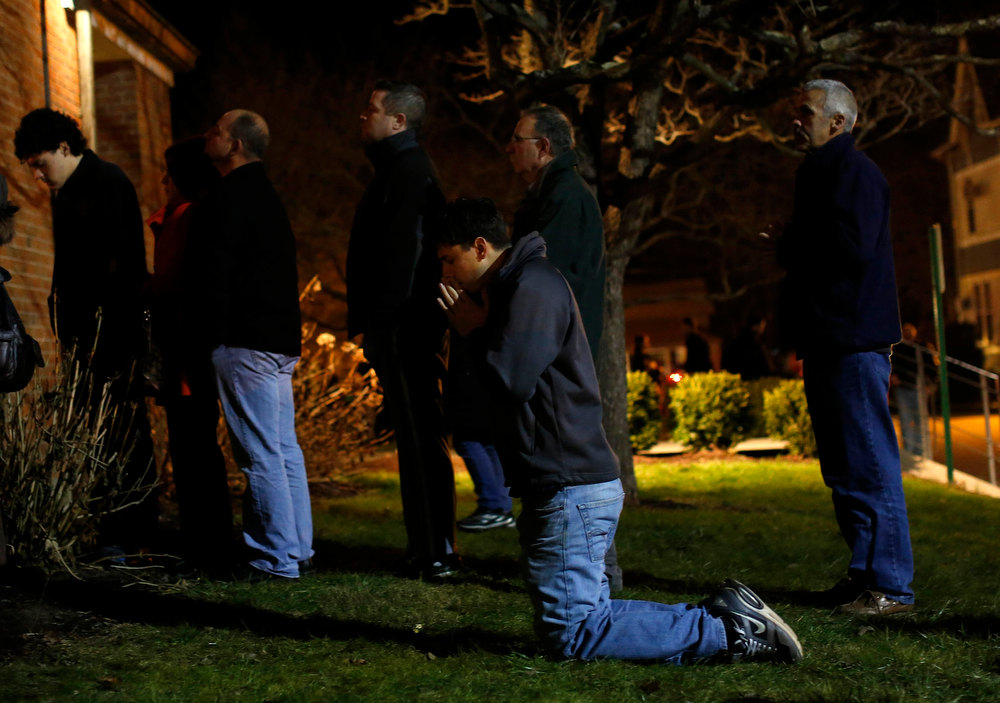 . People pray and stand outside the overflow area of a vigil at the Saint Rose of Lima church in Newtown, Connecticut December 14, 2012. The peace and security of the suburban Connecticut community of Newtown lay shattered on Friday after a gunman attacked a primary school in one of the worst mass shootings in U.S. history. Tearful parents and children gathered around Sandy Hook Elementary School by midday on Friday, surrounded by police vehicles, as young and old alike struggled to make sense of a shooting rampage that killed at least 28 people, including 20 children.  REUTERS/Shannon Stapleton