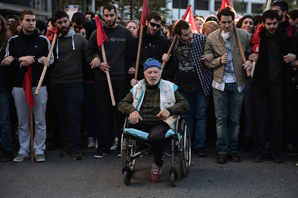 . A man in a wheelchair sits in front of youths holding red flags in central Athens on December 6, 2014, during a protest to commemorate the six-year anniversary of the fatal shooting of teenager Alexis Grigoropoulos by a police officer, an event that plunged Greece into weeks of youth riots. AFP PHOTO / LOUISA GOULIAMAKI/AFP/Getty Images