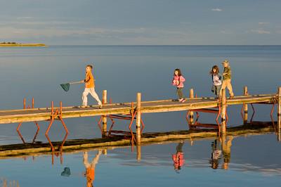Children play on wooden pier overlooking Puck Bay, Hel Peninsula, Baltic Sea, Poland