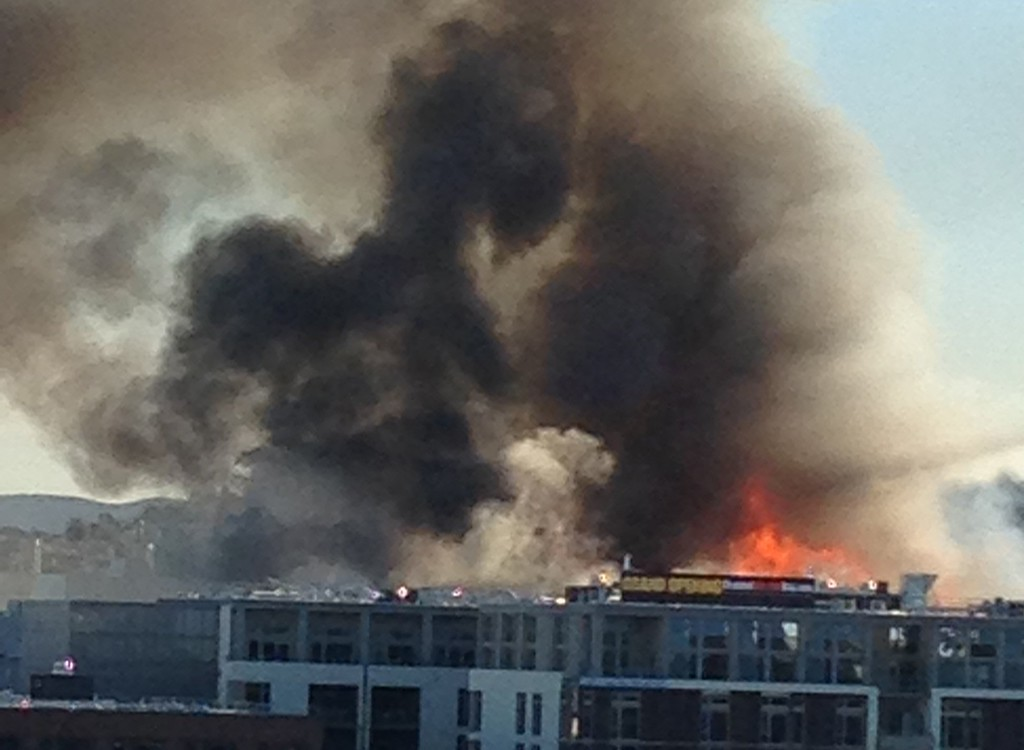. A large fire burning buildings under construction in China Basin, south of AT&T Park is seen from the offices of the San Francisco Giants on Tuesday, March 11, 2014. (Courtesy of Margo Malone)