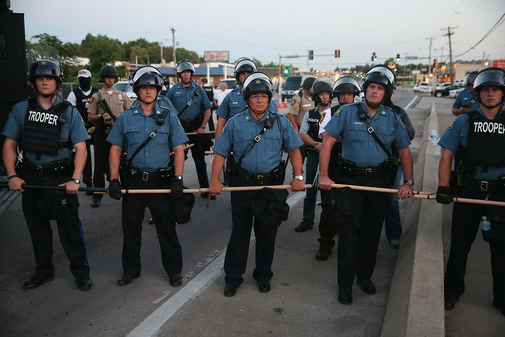 . Police stand watch as demonstrators protest the shooting death of teenager Michael Brown on August 13, 2014 in Ferguson, Missouri. Brown was shot and killed by a Ferguson police officer on Saturday. Ferguson, a St. Louis suburb, is experiencing its fourth day of violent protests since the killing.  (Photo by Scott Olson/Getty Images)