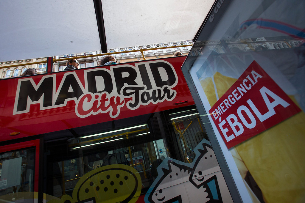 . Tourists travel on a Madrid City tour bus as an advertising calling for financial help to fight Ebola in Africa is displayed on a bus stop in Madrid, Spain, Tuesday, Oct. 7, 2014.  (AP Photo/Andres Kudacki)