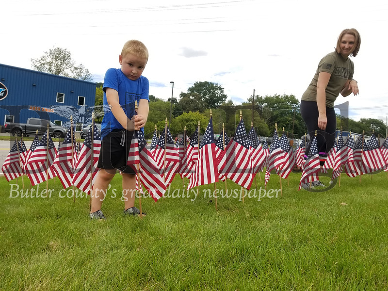 As his mother Megan Klingensmith watches, Grady, places one flag in a memorial of 660 that represents the total number of veterans who die by suicide each month.