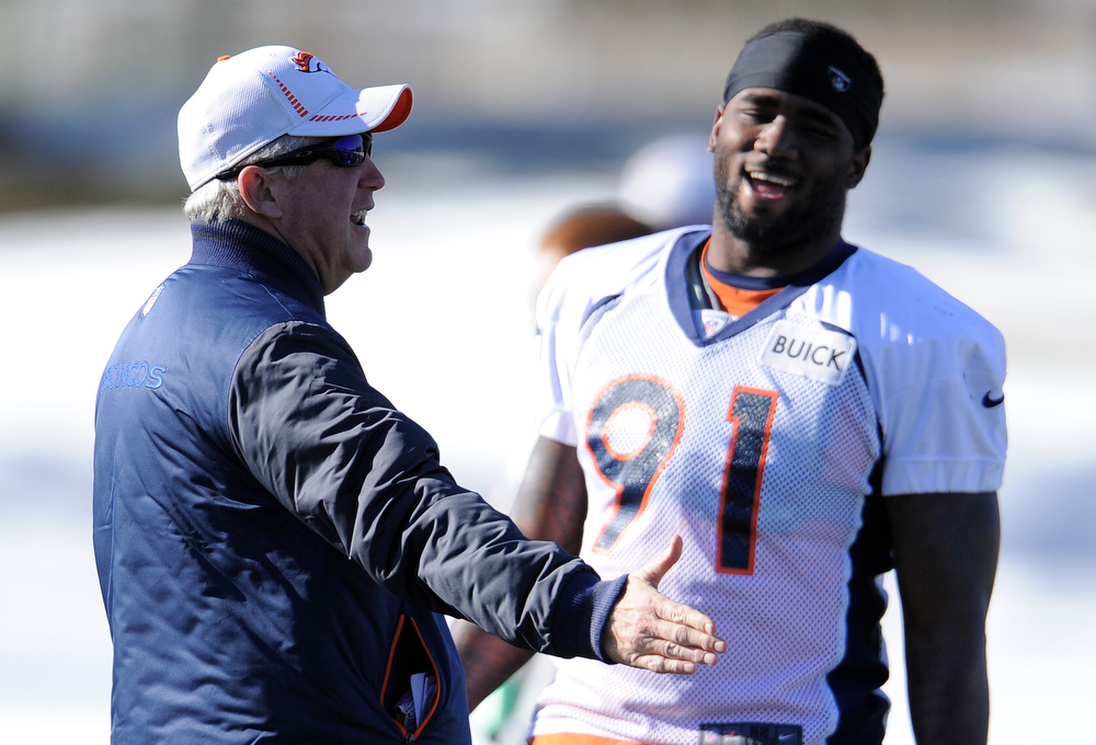 . Denver Broncos head coach John Fox talks with Denver Broncos defensive end Robert Ayers (91)  during practice Thursday, December 20, 2012 at Dove Valley.  John Leyba, The Denver Post