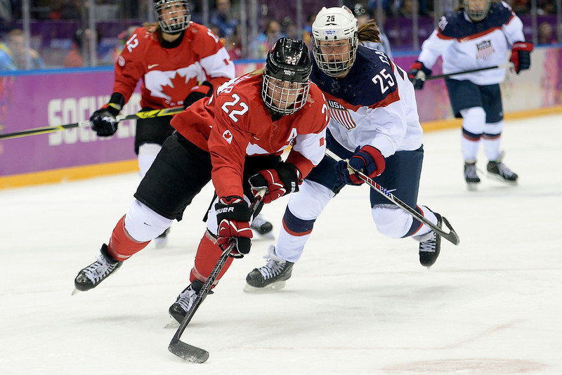 . Hayley Wickenheiser (22) of the Canada controls the puck as Alex Carpenter (25) of the U.S.A. pursues during the first period of the women\'s gold medal ice hockey game. Sochi 2014 Winter Olympics on Thursday, February 20, 2014 at Bolshoy Ice Arena. (Photo by AAron Ontiveroz/ The Denver Post)
