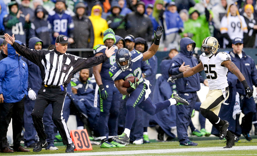 . Seattle Seahawks running back Robert Turbin, center, runs out of bounds in front of New Orleans Saints free safety Rafael Bush (25) during the first half of an NFC divisional playoff NFL football game in Seattle, Saturday, Jan. 11, 2014. (AP Photo/Ted S. Warren)