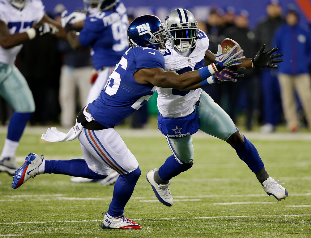 . New York Giants strong safety Antrel Rolle, left, intercepts a pass intended for Dallas Cowboys wide receiver Dez Bryant, right, during the first half of an NFL football game Sunday, Nov. 24, 2013, in East Rutherford, N.J. (AP Photo/Seth Wenig)