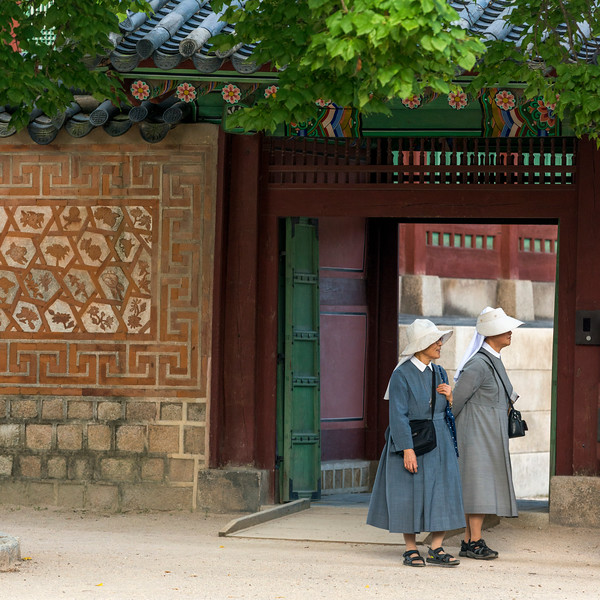Two women at the entrance of Gyeongbokgung Palace, Seoul, South Korea