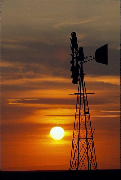 The sun sets behind a wind mill on a farm near Connell, WA.