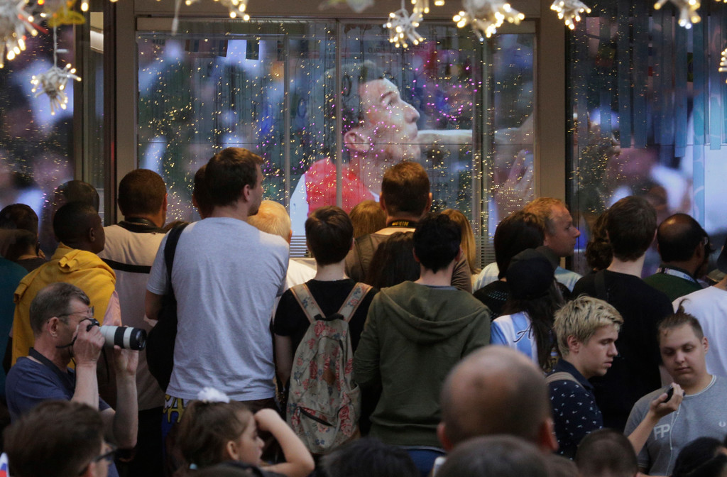 . People watch the final match between France and Croatia at the 2018 soccer World Cup trough a window of a bar in Moscow, Russia, Sunday, July 15, 2018. (AP Photo/Dmitri Lovetsky)