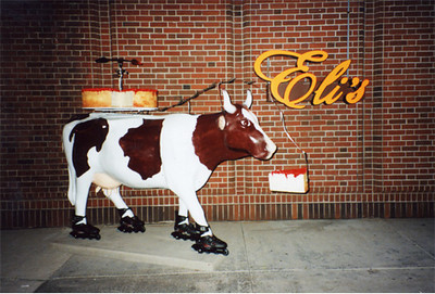 """We made this cow for Chicago's Cows On Parade. We were hired by Eli's Cheese Cake. The cow is wearing Roller Blades and sports a giant cheese cake on it's back. On top to the cheese cake is a whirli-gig made up of pie server and a """"fishing pole"""" of forks goads the cow forward. One spot on the cow is in the shape of the state of Illinois and the other is in the shape of Lake Michigan."""