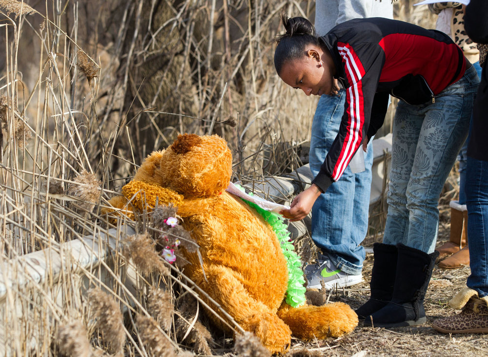 . Mindy Morgan reads a note at the memorial where six teens were killed in a car crash on Park Ave. in Warren, Ohio on Sunday, March 10, 2013. (AP Photo/Scott R. Galvin)