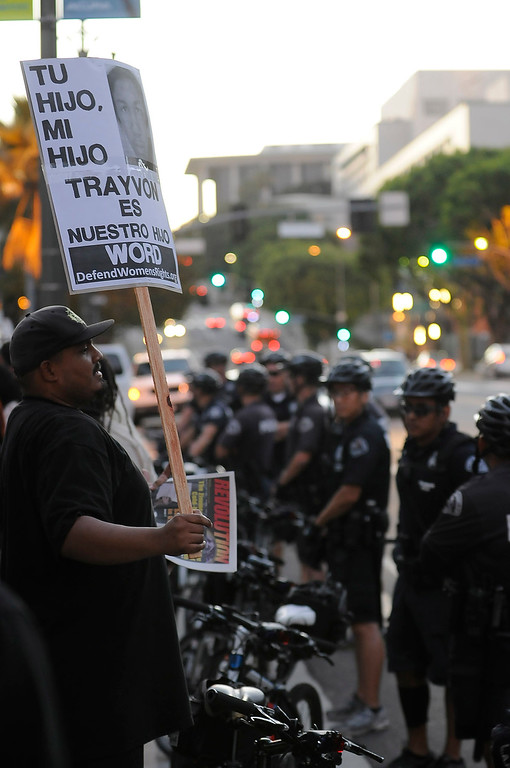 . A protestor faces a group of LAPD bicycle officers after the march. A group of nearly 100 people, protesting the Trayvon Martin verdict, gathered at Los Angeles City Hall, and then marched a circular route that concluded at the Police Administration Building in Los Angeles, CA. 7/16/2013(John McCoy/LA Daily News)