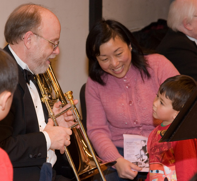 Charlie Phillips, trombone, with child -- Hopkins Symphony Orchestra, March 2008
