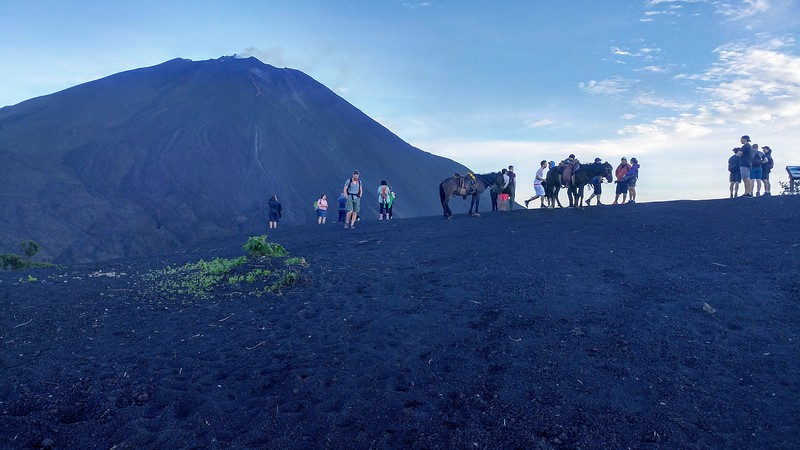 people and horses standing on black earth with volcano in the background