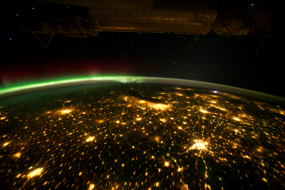 Description of . This astronaut photograph highlights the Chicago metropolitan area as the largest cluster of lights, next to the dark patch of Lake Michigan. The other largest metropolitan areas include St. Louis, Minneapolis–St. Paul, and the Omaha–Council Bluffs region on the Nebraska–Iowa border. The northeastern seaboard lies just beyond the Appalachian Mountains, a dark winding zone without major cities.  The artificial light from human settlements appears with a characteristic yellow tinge. The green light of the aurora borealis also shines brightly in this view—even seeming to reflect off Earth's surface in Canada. A small white patch of light is almost certainly lightning from a storm on the East coast (image top right). Part of the International Space Station (ISS) appears across the top of the image. (Photo by NASA)