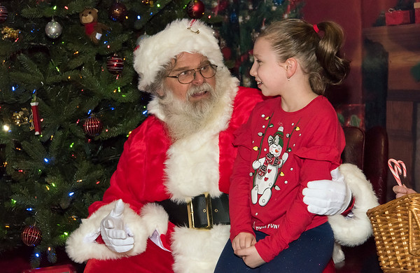 12/06/18 Wesley Bunnell | Staff Plainville held a tree lighting ceremony on Thursday at Fire HQ featuring singing, refreshments and a visit from Santa with a chance to sit on his lap. Gonna Agudelo, age 9, sits on Santa's lap.
