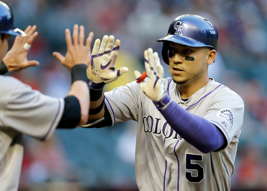 . Colorado Rockies\' Carlos Gonzalez (5) crosses the plate after hitting a two-run home run against the Arizona Diamondbacks during the first inning of a baseball game on Wednesday, April 30, 2014, in Phoenix. (AP Photo/Matt York)