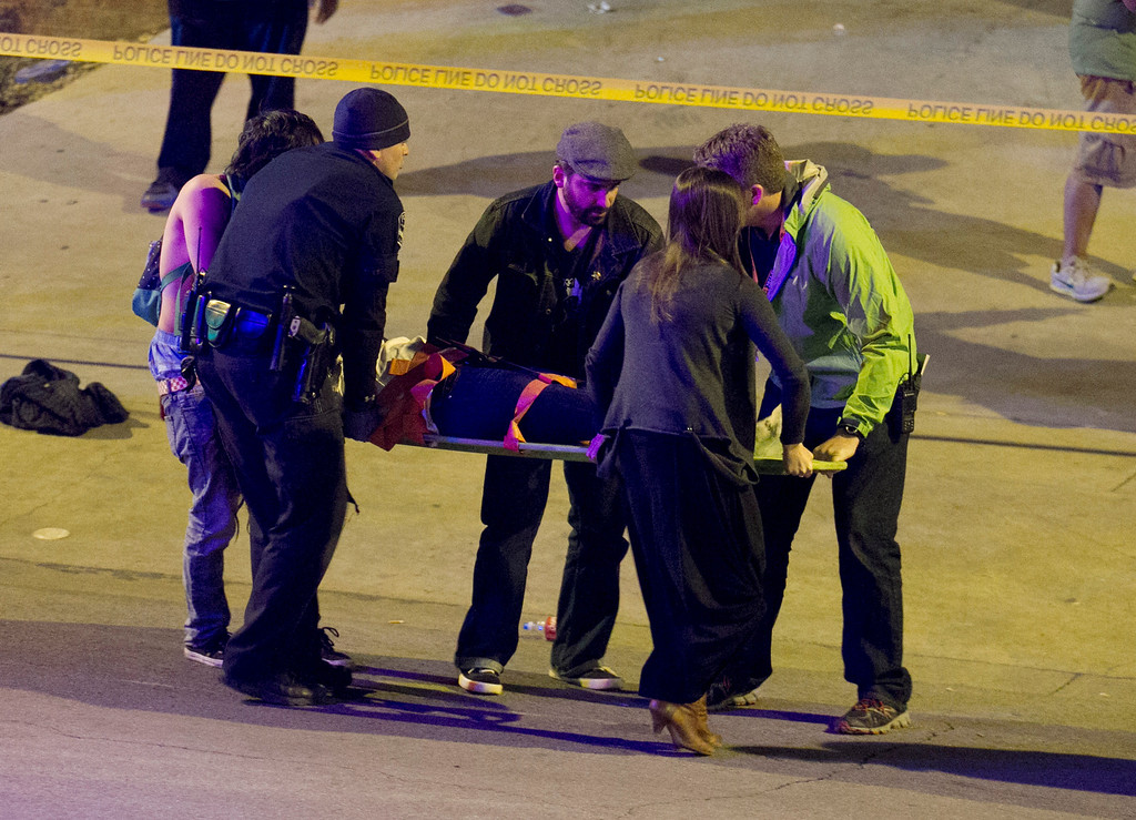. Bystanders and a police officers move a person who was struck by a car on Red River Street in downtown Austin, Texas, at SXSW on Wednesday March 12, 2014.  (AP Photo/Austin American-Statesman, Jay Janner)