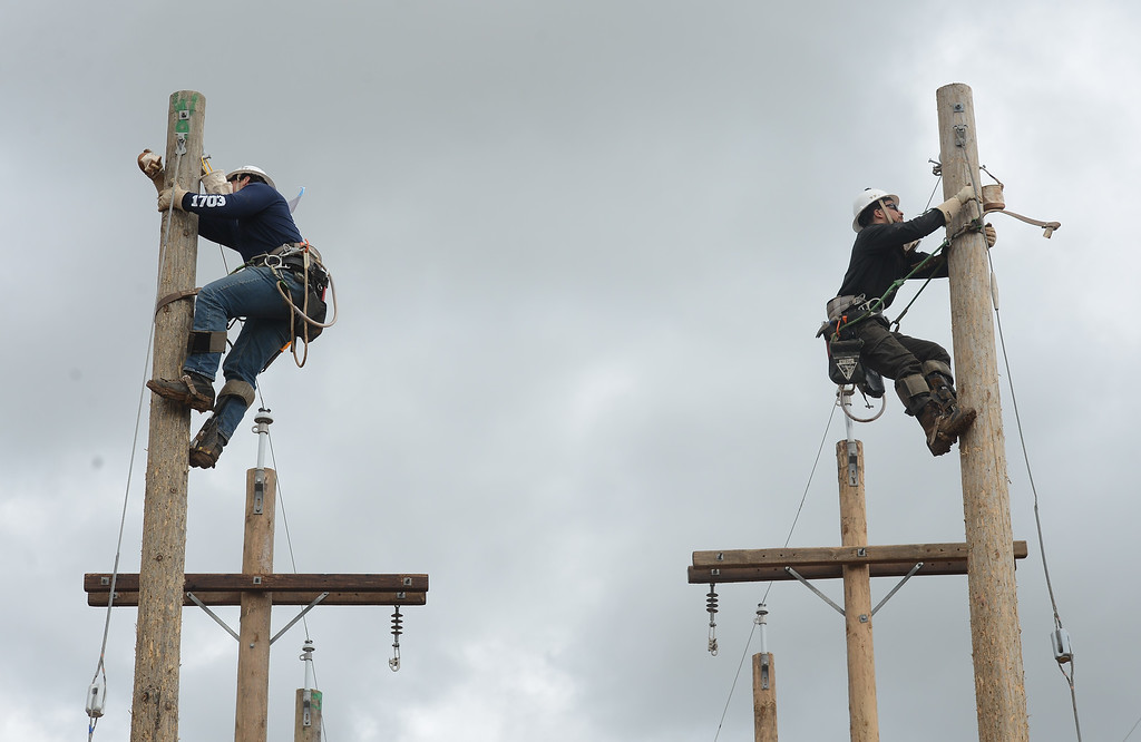 . Brady Zuniga (left) and Deonte Gonzales (right) race up poles during the Northwest Lineman College\'s graduation rodeo, March 15, 2018, in Chico, California. (Carin Dorghalli -- Enterprise-Record)