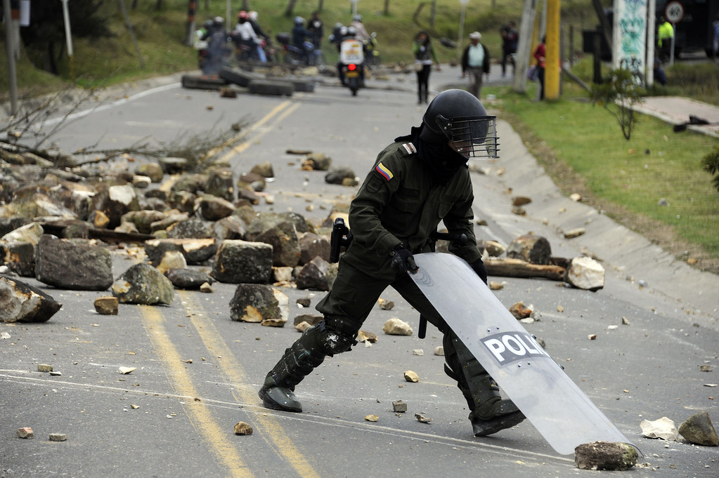 . A Colombian police officer clears a road blocked set by farmers demanding government subsidies and greater access to land, in La Calera, Cundinamarca department, on August 23, 2013. A five-day-old farmworkers\' protest in Colombia claimed its first fatality Friday when a man on a motorcycle crashed and died at a roadblock, police said Friday. Since the protests began Monday, farmworkers have closed roads at dozens of points in across the country, blocking the passage of cargo trucks and other vehicles from makeshift camps erected on sides of roads. EITAN ABRAMOVICH/AFP/Getty Images