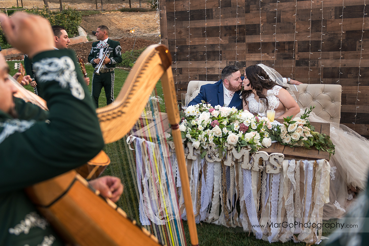 bride and groom kissing at sweetheart table during outdoor wedding recetpion at Taber Ranch Vineyards