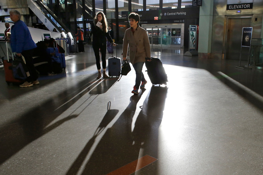 . Travelers pull luggage as they enter a terminal Tuesday, Nov. 22, 2016, at Logan International Airport, in Boston. Almost 49 million people are expected to travel 50 miles or more for the holiday, the most since 2007, according to AAA. (AP Photo/Steven Senne)