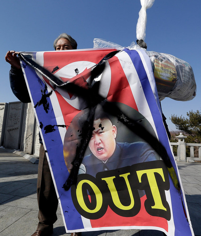 . A South Korean activist shows a defaced portrait of North Korean leader Kim Jong Un before hanging it to helium balloons with leaflets, during an anti-North Korea rally denouncing North Korea\'s third nuclear test at the Imjingak Pavilion near the border village of Panmunjom, in Paju, north of Seoul, South Korea, Saturday, Feb. 16, 2013. They flew the 200,000 propaganda leaflets across the border to denounce North Korea\'s third nuclear test and late leader Kim Jong Il\'s birthday on Saturday. (AP Photo/Lee Jin-man)