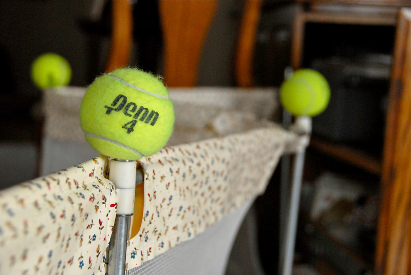 2011/3/12 – This fence is to keep Logan's dogs out of the family room. The tennis balls are to make sure Olin doesn't poke an eye out on the posts. We don't play tennis so I have no idea where we got the tennis balls.