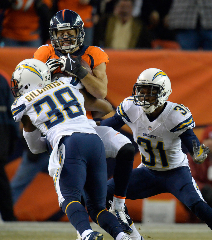 . Denver Broncos wide receiver Eric Decker (87) is hit after a catch by San Diego Chargers strong safety Marcus Gilchrist (38) during the first quarter. The Denver Broncos vs. the San Diego Chargers at Sports Authority Field at Mile High in Denver on December 12, 2013. (Photo by John Leyba/The Denver Post)