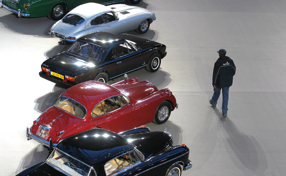 . A visitor walks past vintage and classic cars displayed by Bonhams auction house during an exhibition in Paris, at the Grand Palais in Paris, Wednesday, Feb. 6, 2013. (AP Photo/Jacques Brinon)