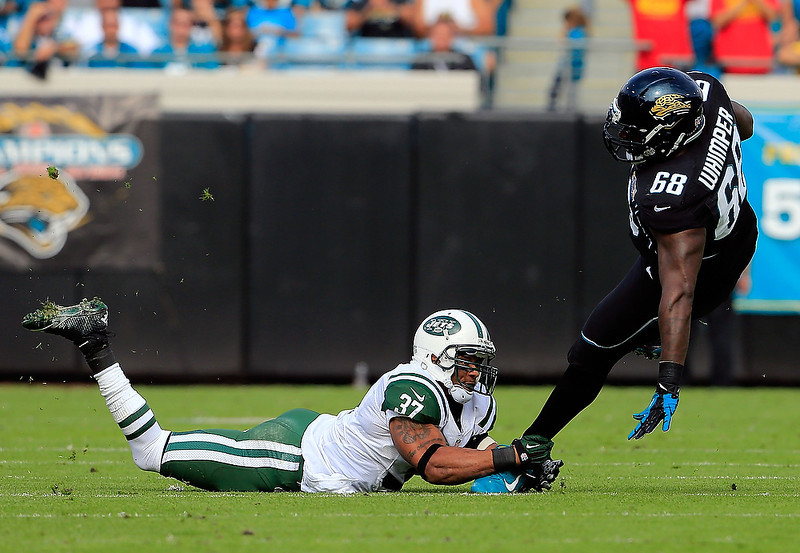 . JACKSONVILLE, FL - DECEMBER 09:   Guy Whimper #68 of the Jacksonville Jaguars is tackled by Yeremiah Bell #37 of the New York Jets during the game at EverBank Field on December 9, 2012 in Jacksonville, Florida.  (Photo by Sam Greenwood/Getty Images)