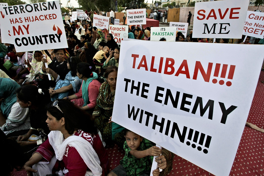 . Pakistani workers of political party Muttahida Qaumi Movement \'MQM\', hold placards during a protest to condemn the killing of foreign tourists by militants, in Karachi, Pakistan, Sunday, June 23, 2013. (AP Photo/Fareed Khan)