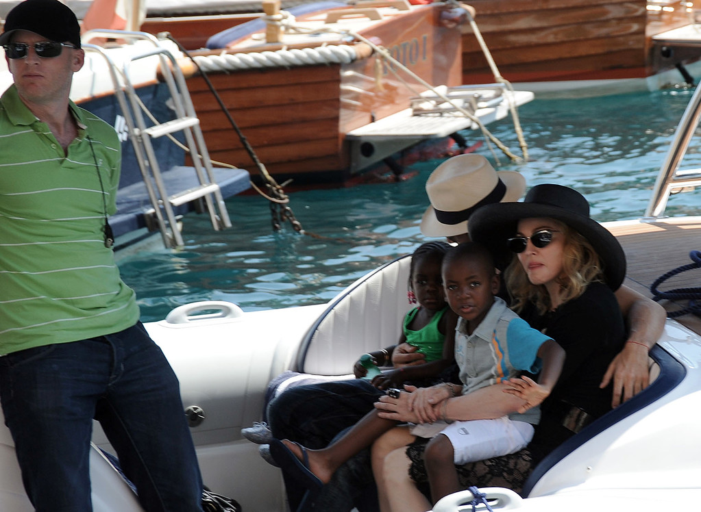 """. Photo taken Monday Aug. 17, 2009 made available Tuesday Aug. 18, 2009 of U.S. singer Madonna, at right, with her adopted child from Malawi David Banda, waving, and Brazilian model Jesus Luz, background with havana hat, holding her other adopted child Chifundo \""""Mercy\"""" James, on a speedboat on their way to see friends on a yacht, in Italy\'s northwestern riviera town of Portofino. Man at left is unidentified. Reports said Tuesday Madonna is in the seaside resort town to spend some time with Italian designers Dolce and Gabbana and other friends. After adopting David Banda in 2008, Malawi\'s highest court had granted the adoption of Chifundo \""""Mercy\"""" James June 12, 2009 overturning an April lower court ruling that Madonna had not spent enough time in Malawi to be given a child. Madonna\'s Raising Malawi, a charity founded in 2006, helps feed, educate and provide medical care for some of Malawi\'s orphans.  (AP Photo)"""