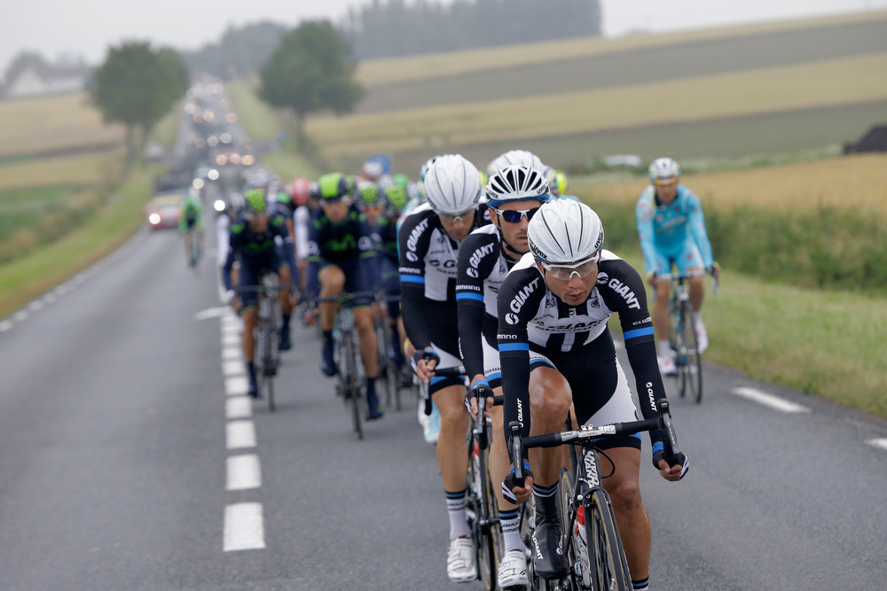 . China\'s Cheng Ji, center, sets the pace as he leads the pack during the sixth stage of the Tour de France cycling race over 194 kilometers (120.5 miles) with start in Arras and finish in Reims, France, Thursday, July 10, 2014. (AP Photo/Laurent Cipriani)