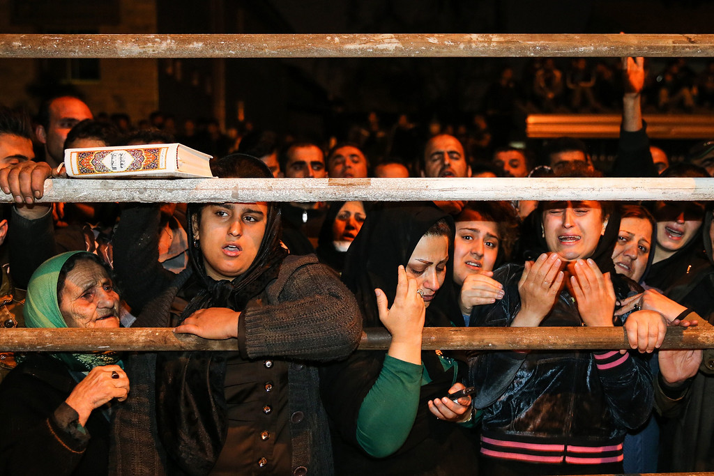 . Iranian women pray for forgiveness as Balal, an Iranian man who killed a fellow Iranian Abdolah Hosseinzadeh in a street fight with a knife in 2007, is brought to the gallows during his execution ceremony in the northern city of Nowshahr on April 15, 2014. AFP PHOTO/ARASH KHAMOOSHI/AFP/Getty Images