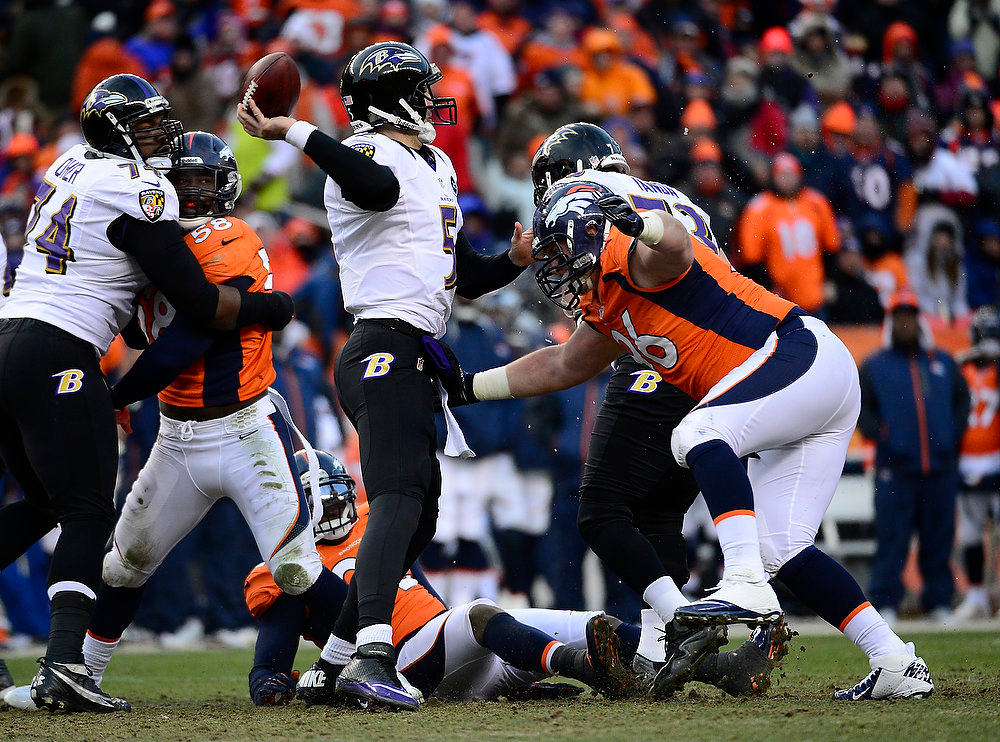 Description of . Baltimore Ravens quarterback Joe Flacco (5) makes a pass as Denver Broncos defensive tackle Mitch Unrein (96) moves in for a tackle in the second quarter. The Denver Broncos vs Baltimore Ravens AFC Divisional playoff game at Sports Authority Field Saturday January 12, 2013. (Photo by AAron  Ontiveroz,/The Denver Post)