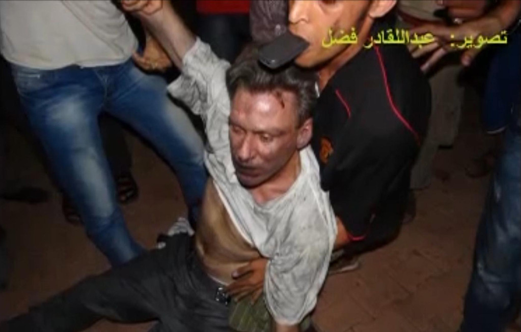 ". In this Sept. 11, 2012 file photo, this still image included in a video obtained by the Associated Press from Fahd al-Bakoush, a freelance videographer and activist, which has been authenticated based on its contents and other AP reporting, shows the body of U.S. Ambassador Chris Stevens being moved by Libyan civilians trying to rescue him after gunmen and protesters rampaged through the U.S. consulate in Benghazi, Libya. The group of Libyans had stumbled across Stevens\' seemingly lifeless form inside a dark room and didn\'t know who he was, only that he was a foreigner, al-Bakoush and two other witnesses told the AP. The Arabic script in the photo translates into English as, ""photo Fahd al-Bakoush.\"" (AP Photo/Fahd al-Bakoush, File)"