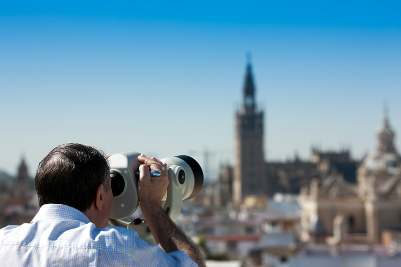 Visitor looking through a telescope at the city of Seville (Spain) from the top of Metropol Parasol